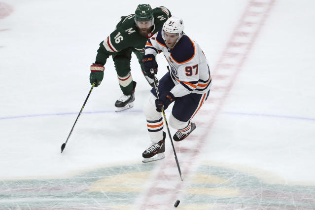 Edmonton Oilers' Connor McDavid (97) controls the puck next to Minnesota Wild's Jason Zucker (16) during the second period of an NHL hockey game Tuesday, Oct. 22, 2019, in St. Paul, Minn. (AP Photo/Stacy Bengs)