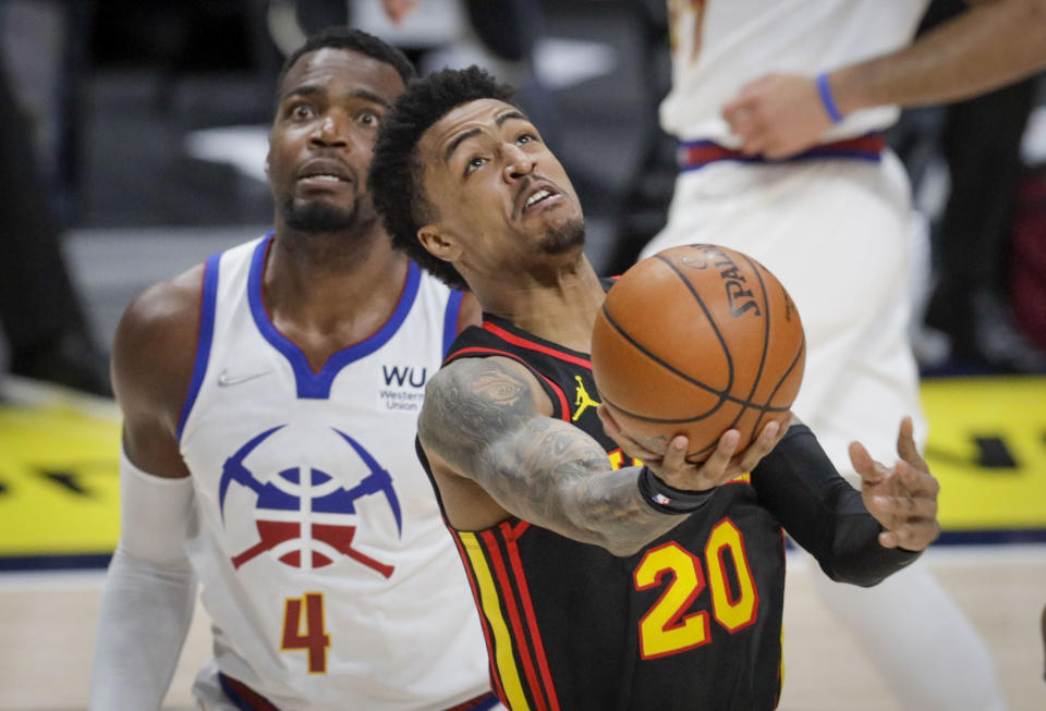 Atlanta Hawks forward John Collins (20) shoots against Denver Nuggets forward Paul Millsap (4) in the second half of an NBA basketball game in Denver, Sunday, March 28, 2021. (AP Photo/Joe Mahoney)