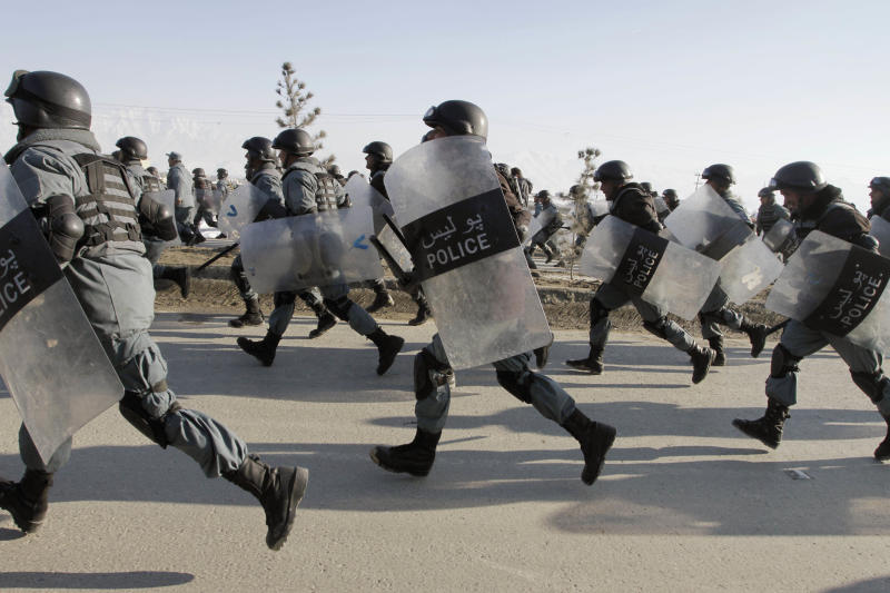 Afghan policemen run after protestors during an anti-U.S. demonstration in Kabul, Afghanistan, Friday, Feb. 24, 2012. Thousands of Afghans staged new demonstrations Friday over the burning of Qurans at a U.S. military base in Afghanistan. (AP Photo/Musadeq Sadeq)
