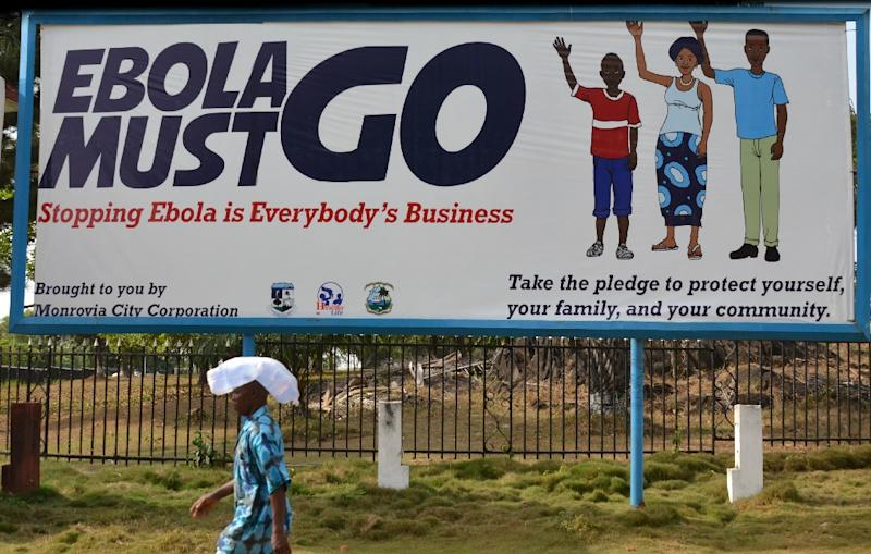 "A man walking past an Ebola campaign banner with the new slogan ""Ebola Must GO"" in Monrovia, Liberia, on February 23, 2015 (AFP Photo/Zoom Dosso)"
