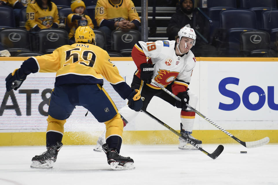 Calgary Flames left wing Matthew Tkachuk (19) looks to pass the puck as he is defended by Nashville Predators defenseman Roman Josi (59), of Switzerland, during the first period of an NHL hockey game Thursday, Feb. 27, 2020, in Nashville, Tenn. (AP Photo/Mark Zaleski)