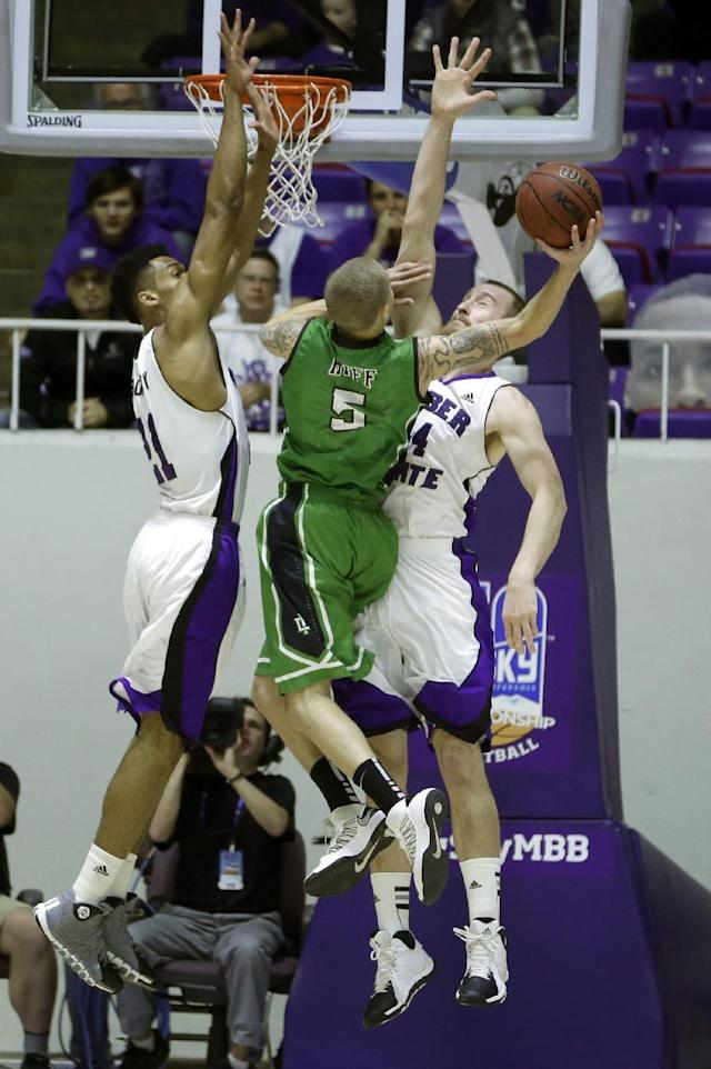 North Dakota's Troy Huff (5) goes to the basket as Weber State's Joel Bolomboy, left, and Kyle Tresnak (44) defend during the first half of an NCAA college basketball game in the championship of the Big Sky Conference tournament Saturday, March 15, 2014, in Ogden, Utah. (AP Photo/Rick Bowmer)