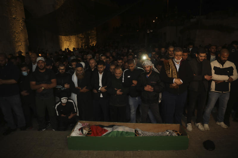 Muslim men pray next to the body of Iyad Halak after Israeli police shot him dead in Jerusalem's old city, Sunday, May 31, 2020. Israel's defense minister has apologized for the Israeli police's deadly shooting of an unarmed Palestinian man who was autistic. (AP Photo/Mahmoud Illean)