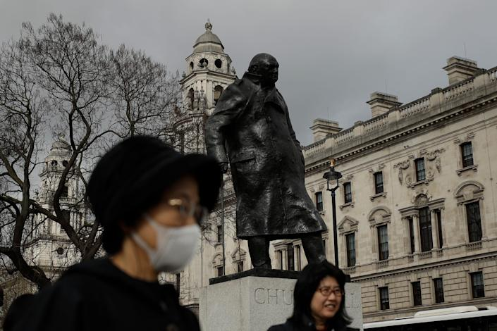 A tourist passes the statue of former British Prime Minister Winston Churchill in Parliament Square in London, where Prime Minister Boris Johnson recently announced he has tested positive for COVID-19.