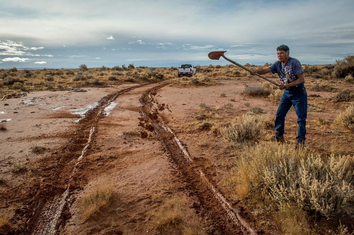 Paul Denetdeal weilding a shovel. 77 percent of reservation roads are unmaintained dirt roads. (Photograph by Mary F. Calvert)