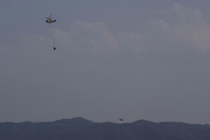 """Helicopters fly over the burned Larnaca mountain region near Ora village, Cyprus, Sunday, July 4, 2021. Cyprus' interior minister says four people have died in what he called the """"most destructive"""" fire in the island nation's history. (AP Photo/Petros Karadjias)"""