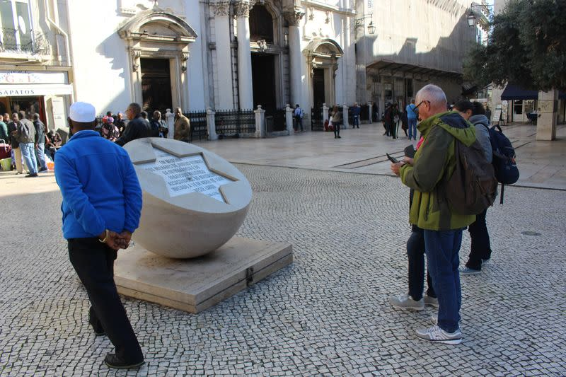 People stand next to a memorial marking the Jewish Massacre of 1506, in Lisbon
