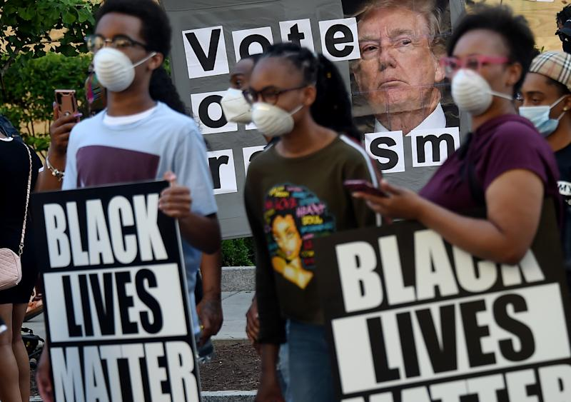 Demonstrators holding Black Lives Matter signs stand by a sign calling to vote out racism with a picture of President Donald Trump, during a peaceful protest against police brutality and the death of George Floyd, on June 7, 2020 in Washington, DC. (Olivier Douliery/AFP via Getty Images)