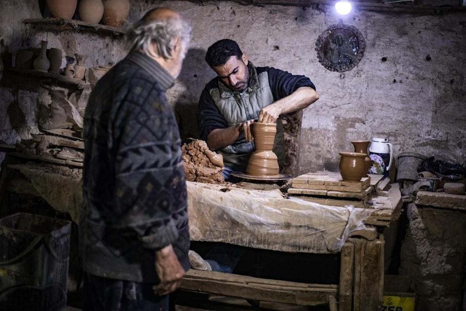 Syrian-Armenian potter Misak Antranik Petros watches his son Anto moulding a clay vase at his workshop near the city of Qamishli on December 19, 2020.