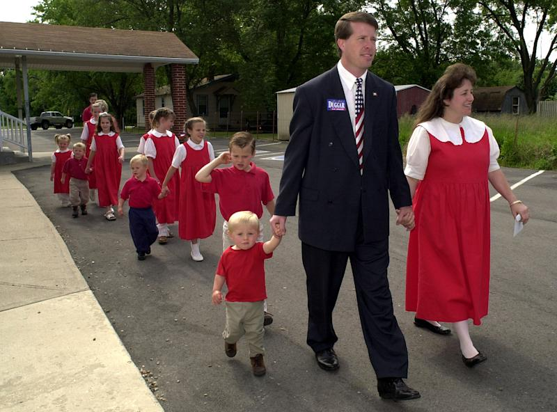 Arkansas state Rep. Jim Bob Duggar of Springdale front center, and his wife Michelle, right, lead twelve of their thirteen children to a polling place in Springdale, Ark., in this Tuesday, May 21, 2002 file photo. Duggar was running for the U.S. Senate against incumbant Tim Hutchinson in the republican primary election. Dugger's sons Jason, 2, is pictured left, followed by Josiah, 5.  (AP Photo/April L. Brown)