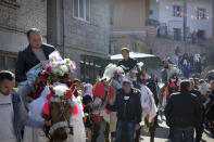Bulgarian muslims take part in a procession during mass circumcision ceremony in the village of Ribnovo, Bulgaria, Sunday, April 11, 2021. Despite the dangers associated with COVID-19 and government calls to avoid large gatherings, Hundreds of people flocked to the tiny village of Ribnovo in southwestern Bulgaria for a four-day festival of feasting, music and the ritual of circumcision which is considered by Muslims a religious duty and essential part of a man's identity. (AP Photo/Jordan Simeonov)