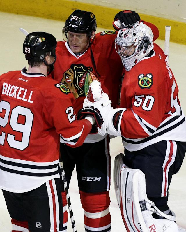Chicago Blackhawks goalie Corey Crawford (50) celebrates with teammates Marian Hossa (81) and Bryan Bickell (29) after they defeated the St. Louis Blues 5-1 in Game 6 of a first-round NHL hockey playoff series in Chicago, Sunday, April 27, 2014. (AP Photo/Nam Y. Huh)