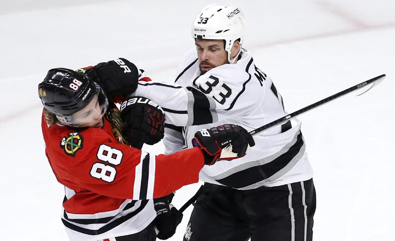 Los Angeles Kings defenseman Willie Mitchell (33) challenges Chicago Blackhawks right wing Patrick Kane (88) during the second period of Game 1 of the Western Conference finals in the NHL hockey Stanley Cup playoffs in Chicago on Sunday, May 18, 2014. (AP Photo/Charles Rex Arbogast)