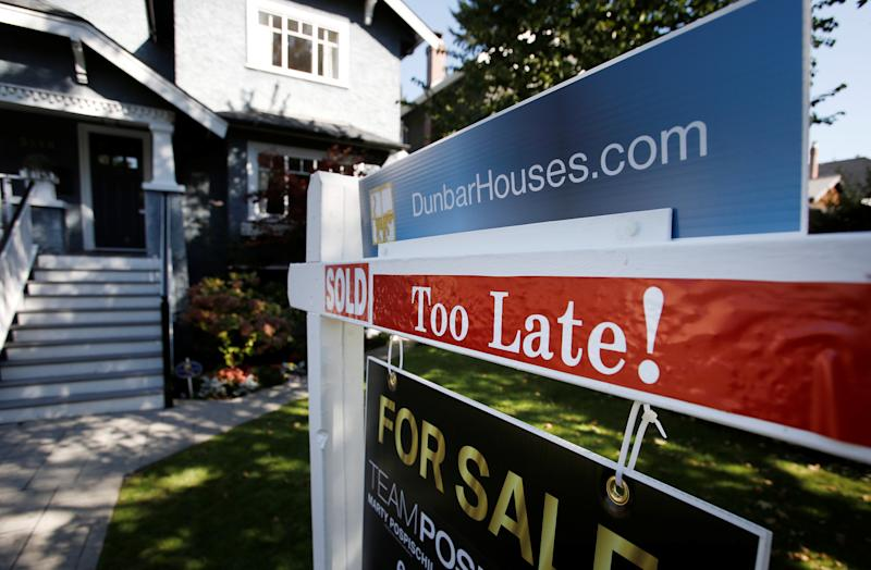 A real estate for sale sign is pictured in front of a home in Vancouver, British Columbia (REUTERS/Ben Nelms)