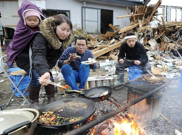 Tsunami survivors cook and eat in front of their damaged house Tuesday, March 15, 2011 in Ishinomaki in Miyagi Prefecture (state) after the area was badly damaged by Friday's massive earthquake and tsunami. (AP Photo/Kyodo News)