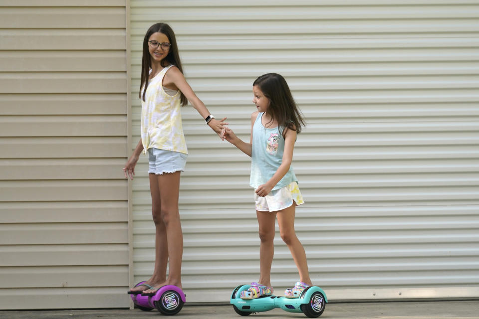 Cecilia Shaffette plays in the driveway with her sister Lydia, right, at their home in Carriere, Miss., Wednesday, June 16, 2021. The 12-year-old is thriving, eight months after getting a portion of her father's liver. She received the transplant after nearly losing her life to internal bleeding (AP Photo/Gerald Herbert)