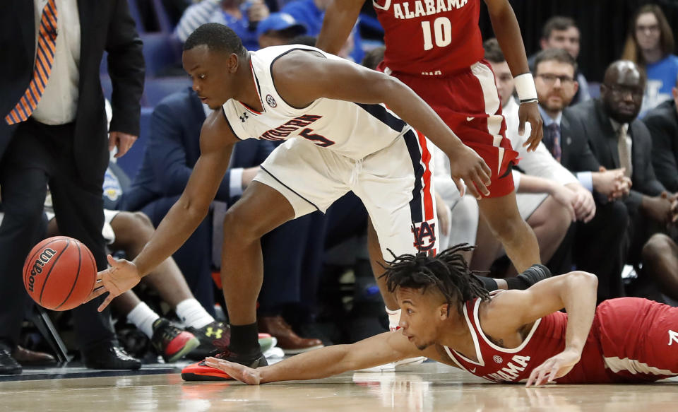 Auburn's Mustapha Heron, top, and Alabama's Dazon Ingram, reach for a loose ball during the first half in an NCAA college basketball quarterfinal game at the Southeastern Conference tournament Friday, March 9, 2018, in St. Louis. (AP Photo/Jeff Roberson)