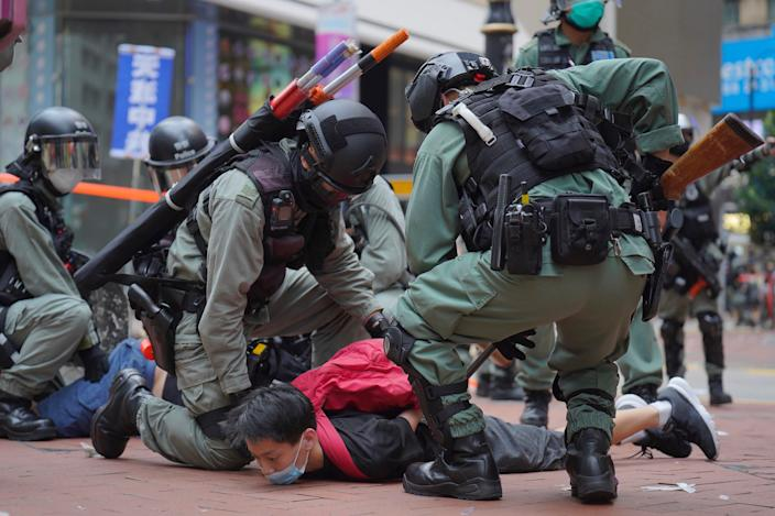 Riot police detain a protester during a demonstration against Beijing's national security legislation in Causeway Bay in Hong Kong on May 24. Hong Kong police fired volleys of tear gas in a popular shopping district as hundreds took to the streets to march.