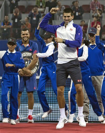 """Serbia's Novak Djokovic, front, performs South Korean rapper PSY's """" Gangnam Style"""" dance with volunteers while Jo-Wilfried Tsonga of France, second from left, looks on after a prize presentation for their men's singles final match of the China Open tennis tournament in Beijing Sunday, Oct. 7, 2012. Djokovic won the China Open tennis tournament, defeated Tsonga 7-6, 6-2. (AP Photo/Andy Wong)"""