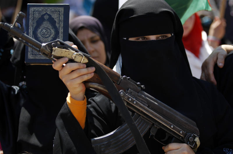 A Syrian woman holds an AK-47 during an anti-Bashar Assad protest after Friday prayers on the outskirts of Idlib, Syria, Friday, June 8, 2012. (AP Photo)