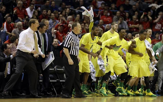 Oregon bench celebrate after Joseph Young (3) shoots a three pointer during the second half of a second-round game in the NCAA college basketball tournament Thursday, March 20, 2014, in Milwaukee. (AP Photo/Jeffrey Phelps)