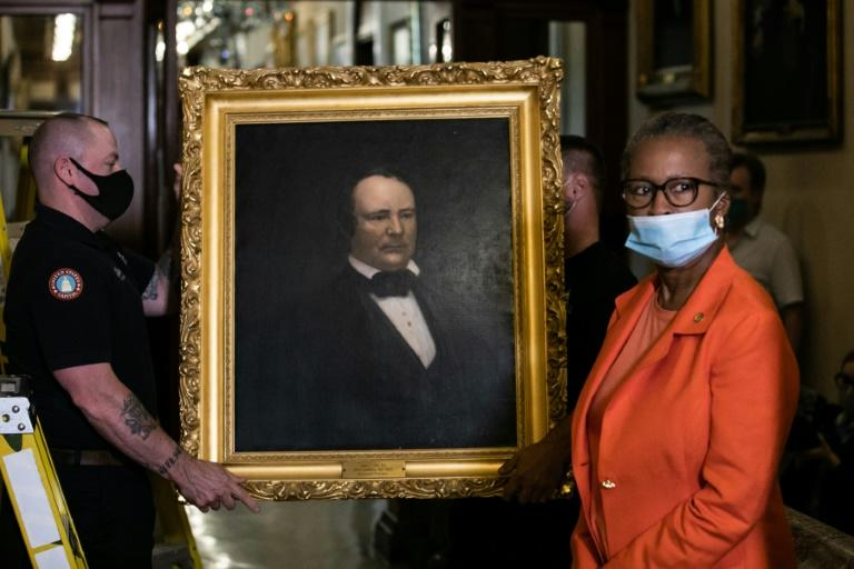 """Workers remove the portrait of former US House speaker James Orr, who served in the Confederacy, from a wall in the US Capitol after current Speaker Nancy Pelosi ordered four such portraits removed because the men symbolized """"grotesque racism"""" (AFP Photo/Graeme Jennings)"""