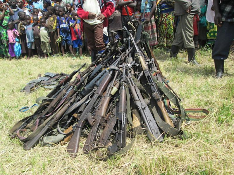 Children and members of the Democratic Forces for the Liberation of Rwanda rebel group stand in front of weapons during an arms surrender ceremony, in Kateku, DR Congo, on May 30, 2014 (AFP Photo/Jean Baptiste Badhera)