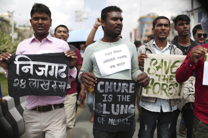 Nepalese activists shout slogans carrying banners of save trees during a protest outside Civil Aviation Authority of Nepal, in Kathmandu, Monday, Aug. 19, 2019. A small group of protesters demonstrated in Nepal's capital against plans to cut down millions of trees for an international airport in the southern part of the country. (AP Photo/Niranjan Shrestha)