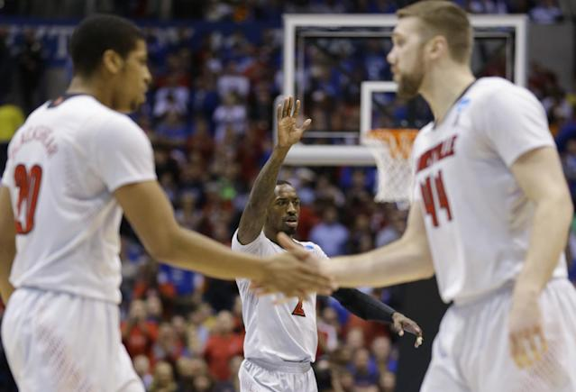 Louisville's Russ Smith (2) celebrates with teammates Wayne Blackshear (20) and Stephan Van Treese (44) during a time out in the first half of an NCAA Midwest Regional semifinal college basketball tournament game against the Kentucky Friday, March 28, 2014, in Indianapolis. (AP Photo/Michael Conroy)
