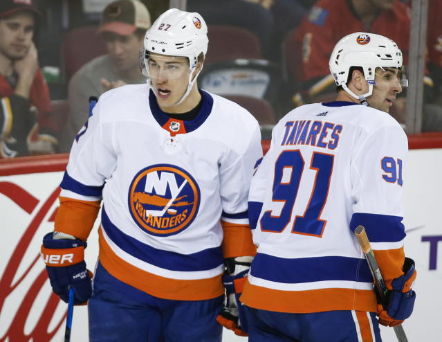 New York Islanders' Anders Lee, left, celebrates his goal with teammate John Tavares during second-period NHL hockey game action against the Calgary Flames in Calgary, Alberta, Sunday, March 11, 2018. (Jeff McIntosh/The Canadian Press via AP)