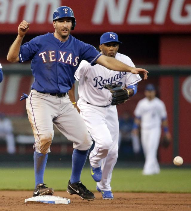 Texas Rangers' Adam Rosales makes it safe to second while Kansas City Royals shortstop Alcides Escobar chases the ball after a throwing error by second baseman Christian Colon during the second inning of a baseball game Tuesday, Sept. 2, 2014, in Kansas City, Mo. (AP Photo/Charlie Riedel)
