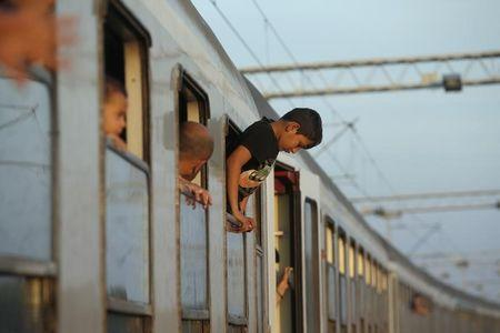 A young migrant hangs out from the window of a train while waiting to depart from the railway station in Tovarnik, Croatia September 22, 2015. REUTERS/Marko Djurica