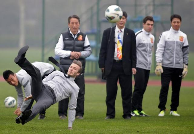 FILE PHOTO: Former England captain David Beckham slips while trying to kick the ball at an event in Wuhan