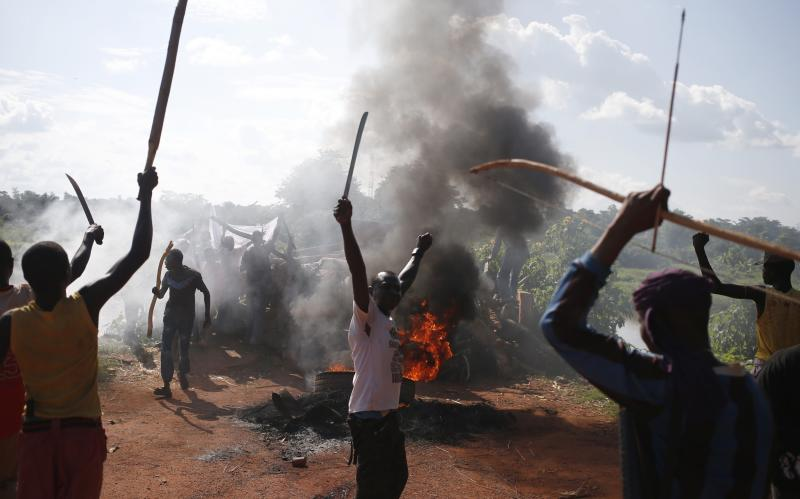 Men gesture in front of a burning barricade during a protest against French soldiers in Bambari