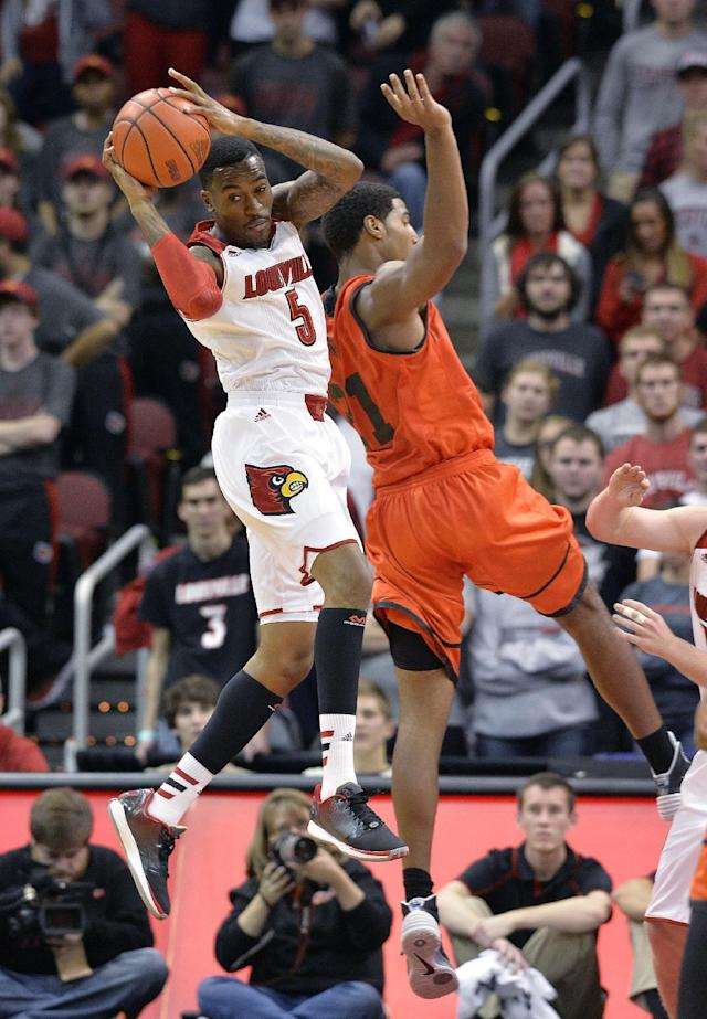Louisville's Kevin Ware, left, pulls down a rebound next to Pikeville's Bruce Reed during the second half of an NCAA college basketball exhibition game, Wednesday, Nov. 6, 2013, in Louisville, Ky. Louisville defeated Pikeville 90-61. (AP Photo/Timothy D. Easley)