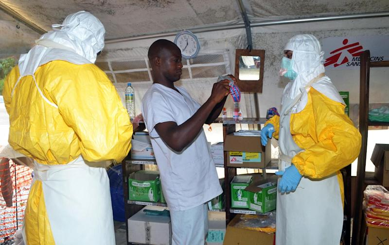 A file picture taken on July 23, 2014 shows health workers putting on protective gear at an Ebola isolation ward in the Guinea capital Conakry, as an outbreak of the disease has so far killed 660 people in west Africa