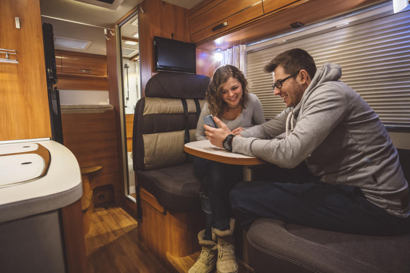 A couple sits inside a contemporary RV.