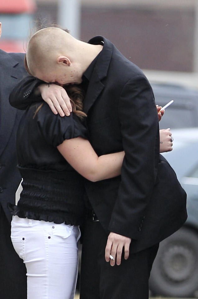 People hug outside of Monreal Funeral Home where calling hours for Daniel Permertor are taking place Friday, March 2, 2012, in Eastlake, Ohio. Parmertor and two others were fatally shot Monday at Chardon High School. Hundreds showed up for his wake at Monreal Funeral Home in Eastlake on Friday, the same day students returned to classes. (AP Photo/Tony Dejak)