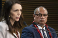 Pacific Peoples Minister Aupito William Sio looks at Prime Minister Jacinda Ardern speak during a post-Cabinet press conference on the 1970's dawn raids at Parliament in Wellington, New Zealand, Monday, June 14, 2021. New Zealand's government is formally apologizing for an immigration crackdown nearly 50 years ago in which Pacific people were targeted for deportation, often after early-morning home raids. (Mark Mitchell/NZ Herald via AP)