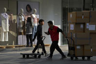 Workers push carts loaded with goods past by an employee adjusts autumn and winter clothing on the mannequins at a fashion boutique in Beijing, Wednesday, Oct. 13, 2021. China's import and export growth slowed in September amid shipping bottlenecks and other disruptions combined with coronavirus outbreaks. (AP Photo/Andy Wong)