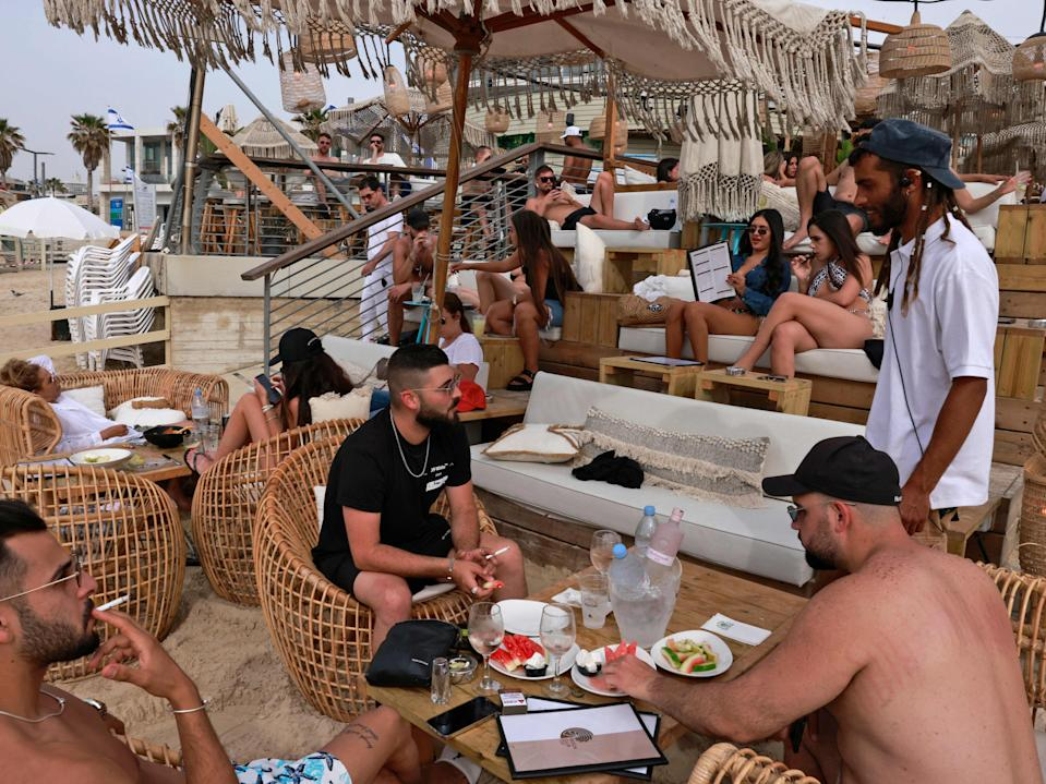 People relax at a beach bar in the Israeli coastal city of Tel Aviv on 19 April after authorities announced face masks were no longer needed outside (AFP via Getty Images)