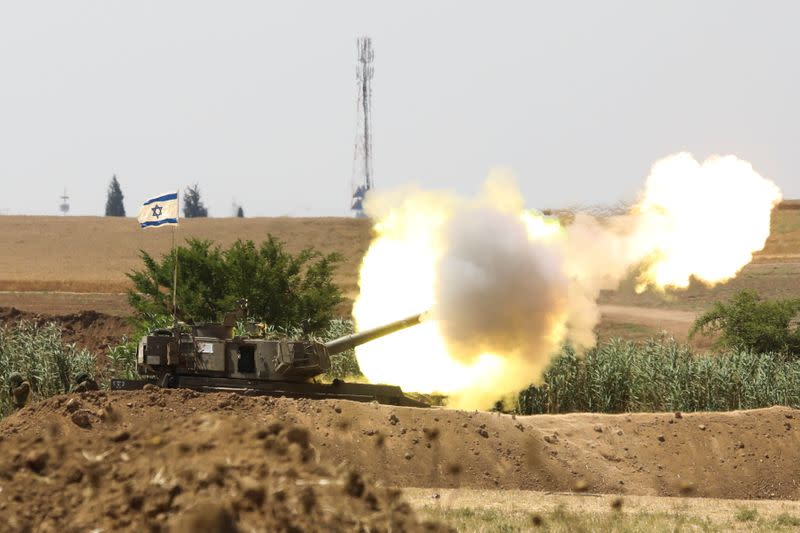 An Israeli flag flutters near an artillery unit as it fires near the border between Israel and the Gaza Strip, on the Israeli side
