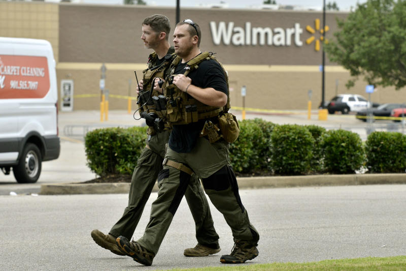 Sheriff Deputies walk through the parking lot after a shooting at a Walmart store Tuesday, July 30, 2019 in Southaven, Miss. A gunman fatally shot two people and wounded a police officer before he was shot and arrested Tuesday at the Walmart in northern Mississippi, authorities said.   (AP Photo/Brandon Dill)
