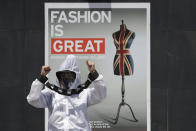 A protester dressed in protective suit with hands tied with mock chains shouts slogans during a rally against the G7 summit outside the British Embassy in Taguig, Philippines on Friday, June 11, 2021. The group called on G7 Summit member nations for debt cancellation for poor countries facing difficulties due to the COVID-19 pandemic. (AP Photo/Aaron Favila)