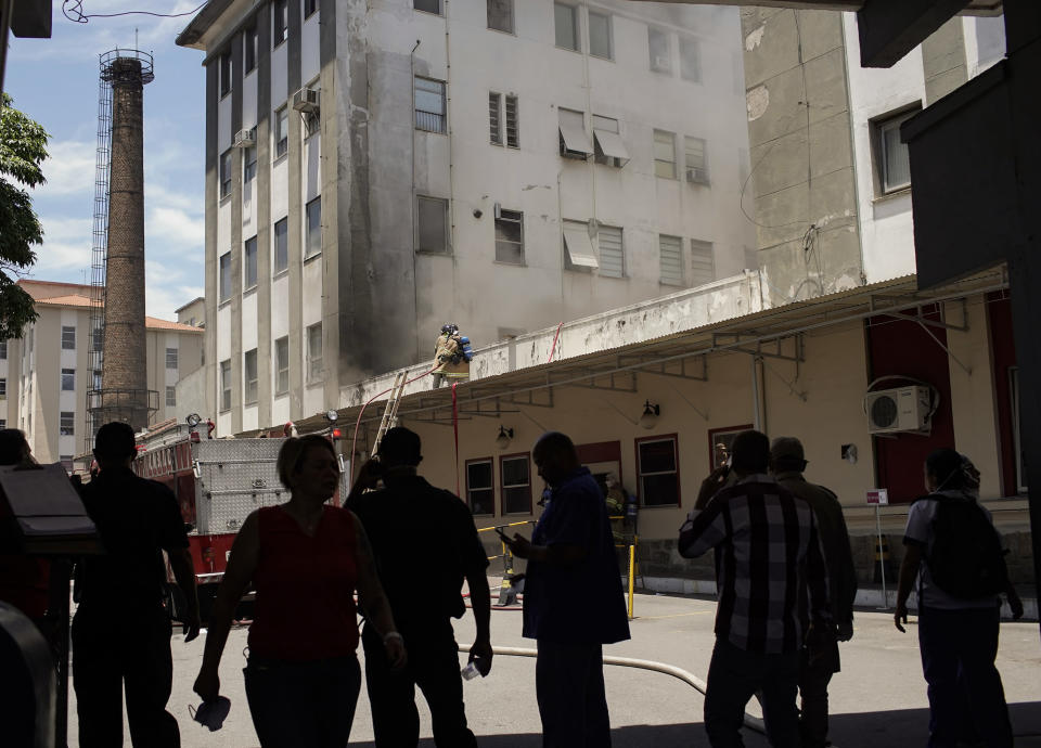 People watch firefighters work to douse a fire that broke out at the Bonsucesso Federal Hospital, which has a COVID-19 wing, in Rio de Janeiro, Brazil, Tuesday, Oct. 27, 2020. According to the fire department, there were no casualties. (AP Photo/Silvia Izquierdo)