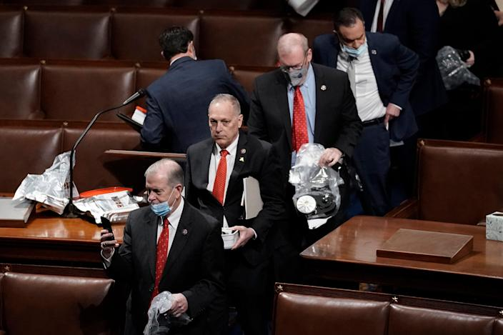House of Representatives members leave the floor of the House chamber as protesters try to break into the chamber at the U.S. Capitol on Jan. 6, 2021, in Washington.