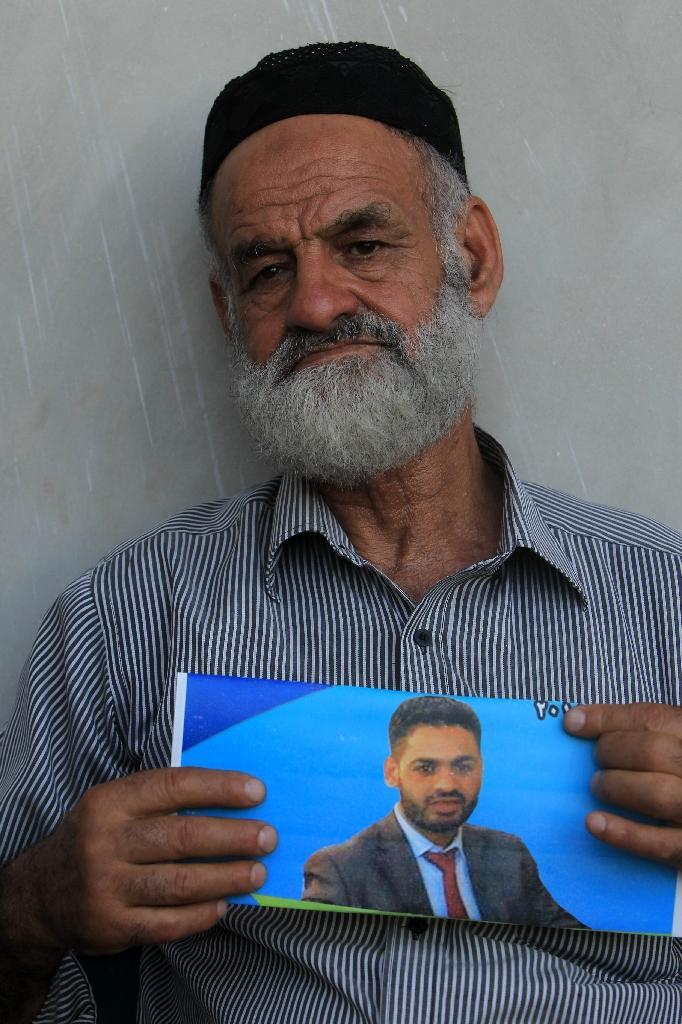 Palestinian Naser al-Deen Allan shows a picture of his son Mohammed Allan, who is held by Israel without trial, at the family home in the West Bank city of Nablus (AFP Photo/Jaafar Ashtiyeh)
