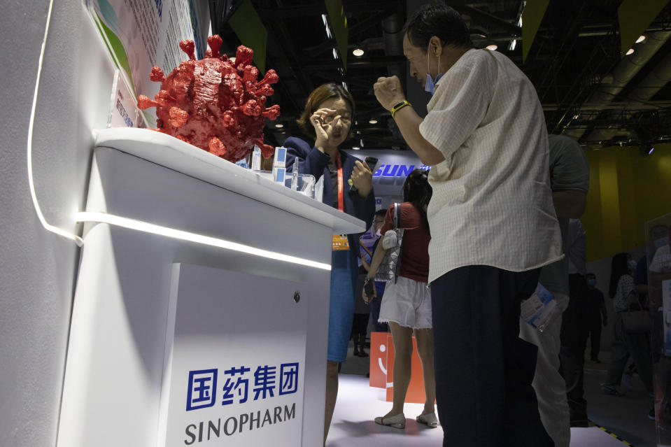 A promoter talks about the COVID-19 vaccine produced by Sinopharm subsidiary CNBG during a trade fair in Beijing on Sunday, Sept. 6, 2020. The Chinese drugmaker said Wednesday, Dec. 30, 2020 its coronavirus vaccine was found to be 79.3% effective at preventing infection in preliminary data from the final round of testing, moving Beijing closer to possibly being able to fulfill its pledge to supply other developing countries.(AP Photo/Ng Han Guan)