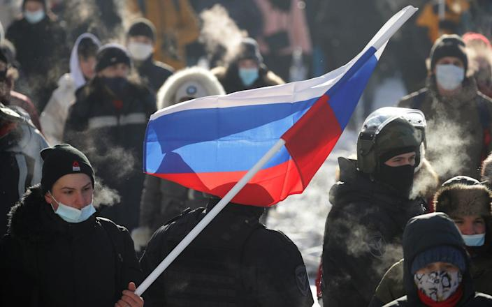 A demonstrator with a Russian national flag takes part in an unauthorised protest - TASS