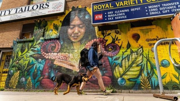 A person walks with their dog in Ottawa on May 11, 2021. (Brian Morris/CBC - image credit)